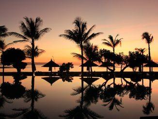 Bild eines Urlaubsortes bei Sonnenuntergang. Palmen und Sonnenschirme spiegeln sich im Wasser